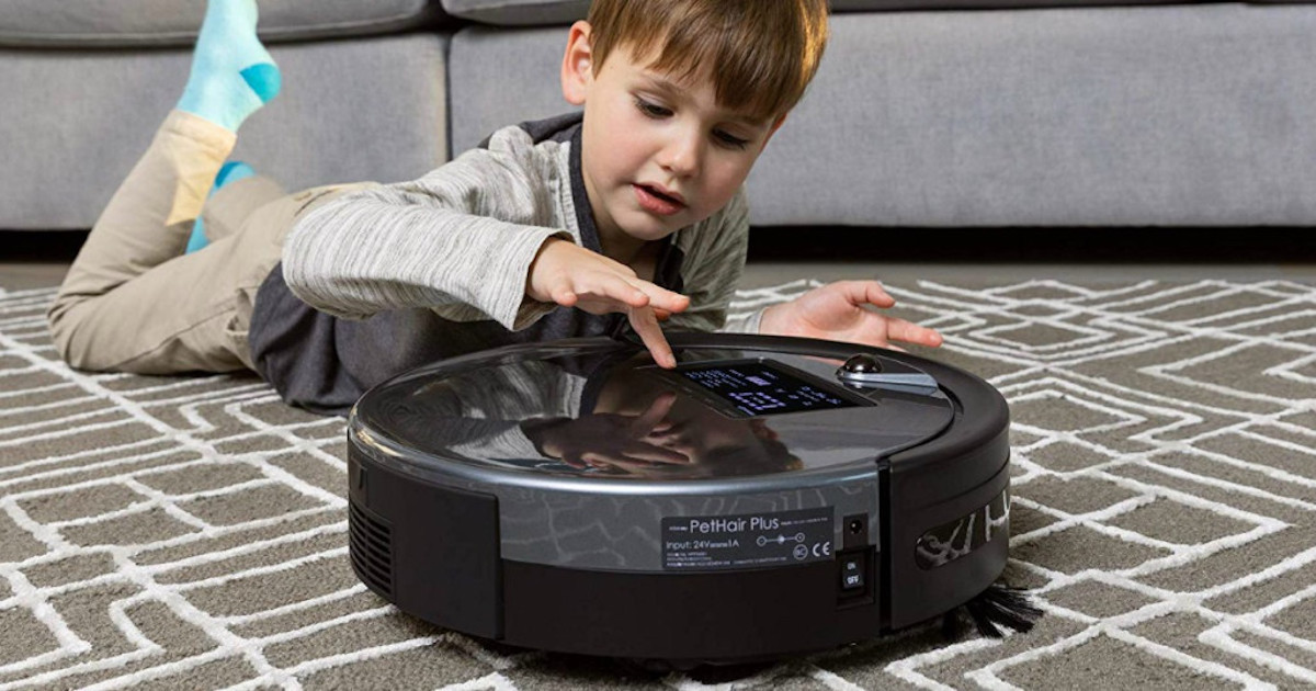 boy child playing with Bobsweep PetHair Plus Robotic Vacuum on carpet