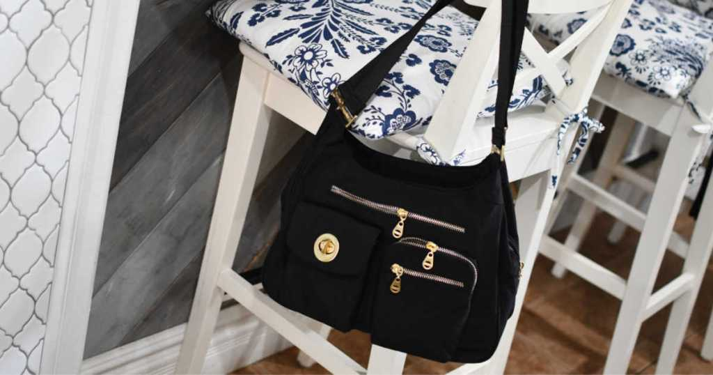 black Baggallini San Marino Satchel hanging on white chair