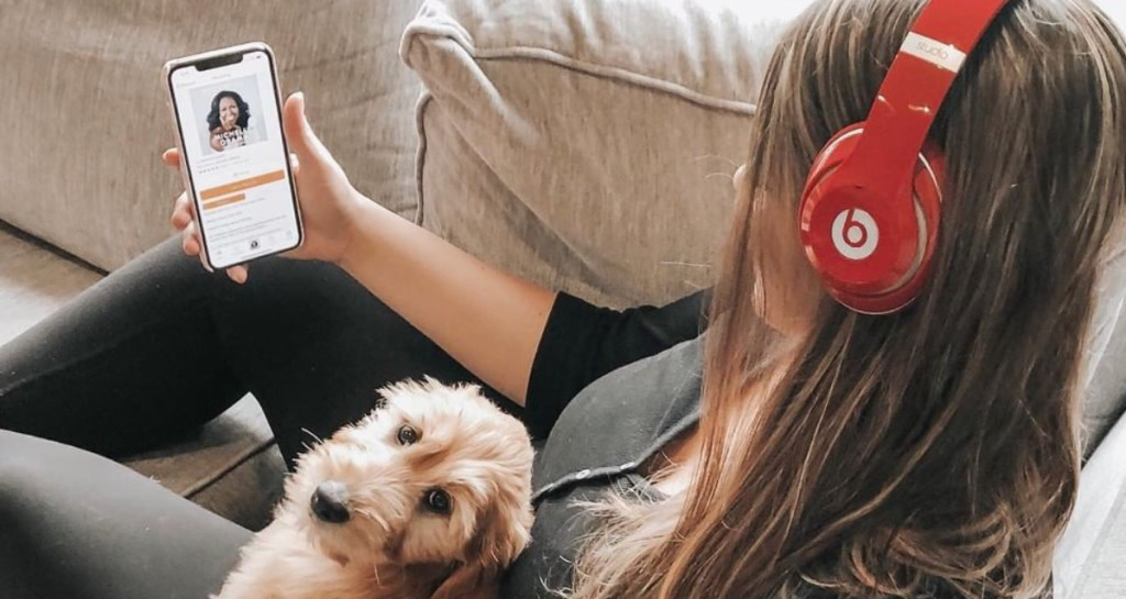 girl with dog listenint to Audible on Beats