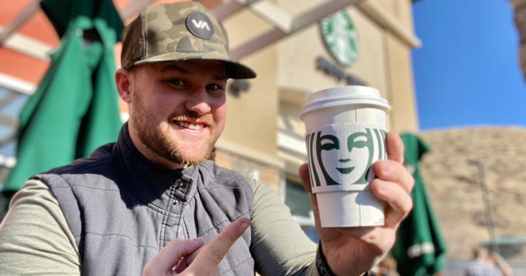 man holding Starbucks cup with one hand and pointing at it with other hand with Starbucks store in background