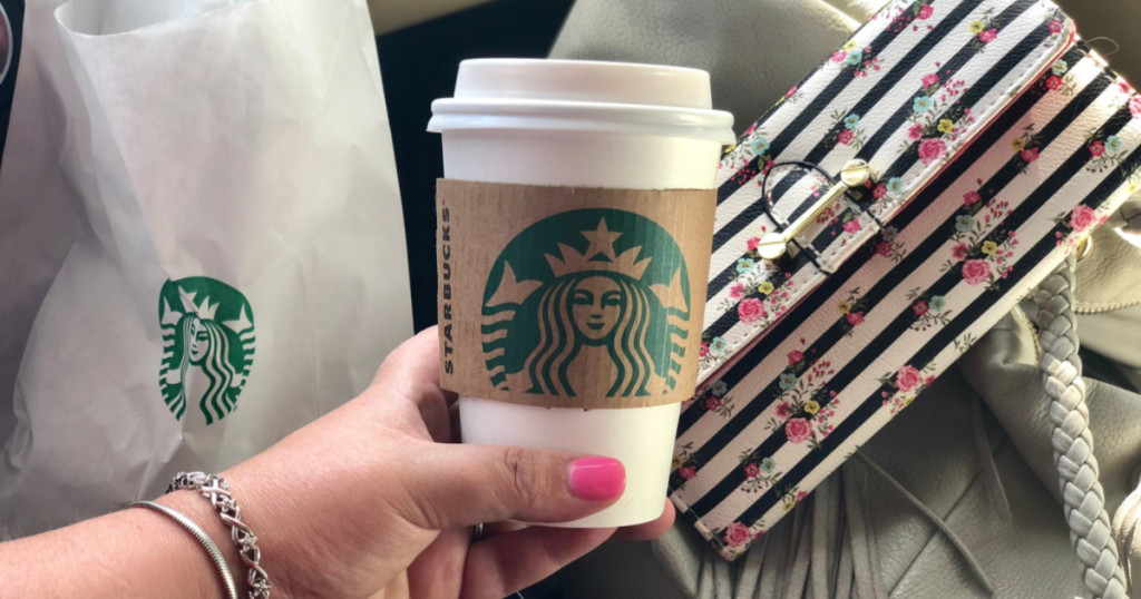 hand with pink nails holding Starbucks cup with Starbucks food bag and floral clutch in background